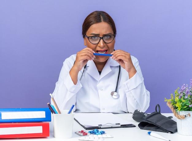 Ärztin mittleren alters im weißen kittel mit stethoskop, die einen stift hält und mit wütendem gesicht am tisch über blauem hintergrund sitzt