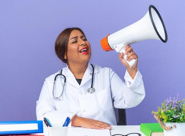 Ärztin mittleren alters im weißen kittel mit stethoskop, die glücklich und aufgeregt am tisch über blauem hintergrund sitzt und megaphon schreit