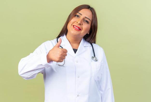 Ärztin mittleren alters im weißen kittel mit stethoskop, die lächelnd selbstbewusst aussieht und daumen nach oben zeigt