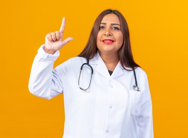 Ärztin mittleren alters im weißen kittel mit stethoskop, die lächelnd selbstbewusst aussieht und zeigefinger zeigt