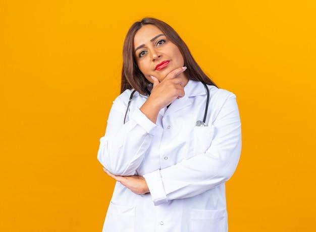 Ärztin mittleren alters im weißen kittel mit stethoskop, die mit nachdenklichem ausdruck mit der hand am kinn schaut