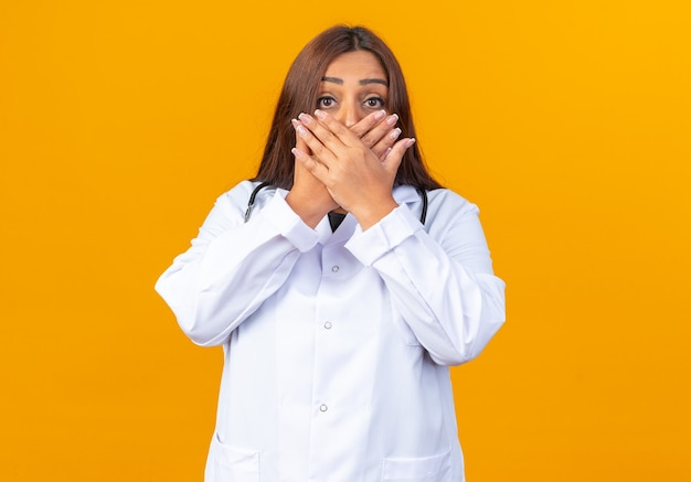 Ärztin mittleren alters im weißen kittel mit stethoskop, die schockiert ist und den mund mit den händen bedeckt, die über der orangefarbenen wand stehen?