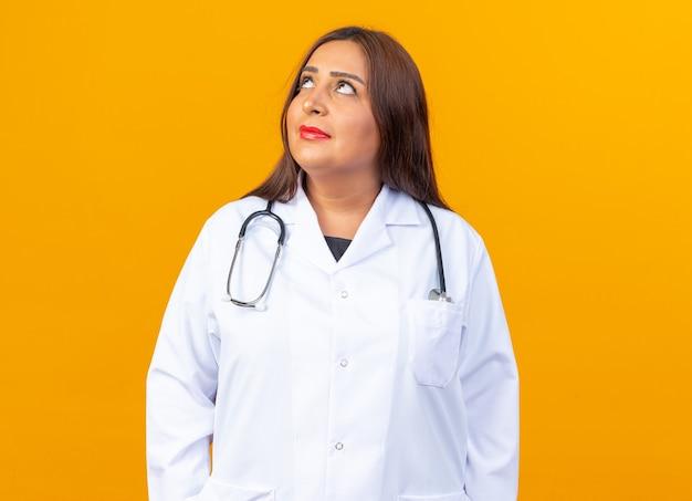 Ärztin mittleren alters im weißen kittel mit stethoskop, die verwirrt aufschaut