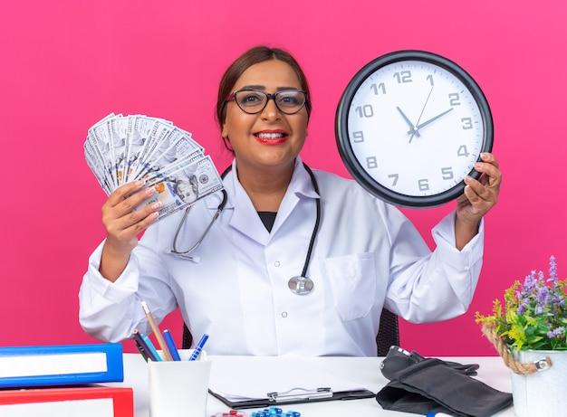 Ärztin mittleren alters im weißen kittel mit stethoskop, die wanduhr und bargeld hält, lächelt fröhlich glücklich und positiv am tisch sitzend auf rosa