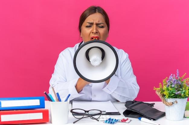 Ärztin mittleren alters im weißen kittel mit stethoskop, die zum megaphon schreit, aufgeregt am tisch sitzend mit büroordnern auf rosa