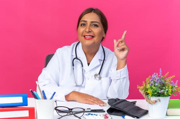 Ärztin mittleren alters im weißen kittel mit stethoskop, die zuversichtlich lächelt und zeigefinger zeigt, der eine neue idee hat, die am tisch mit büroordnern auf rosa sitzt