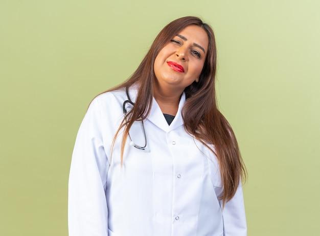 Ärztin mittleren alters im weißen kittel mit stethoskop glücklich und positiv lächelnd zuversichtlich stehend auf grün