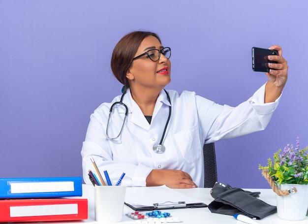 Ärztin mittleren alters im weißen kittel mit stethoskop macht selfie mit smartphone und sieht selbstbewusst lächelnd mit glücklichem gesicht aus, das am tisch über blauer wand sitzt