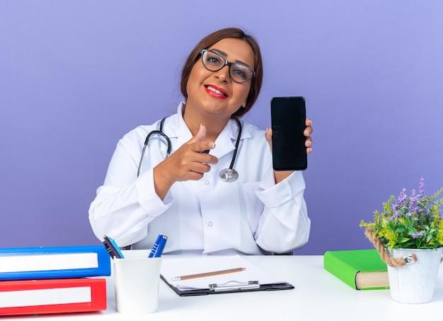 Ärztin mittleren alters im weißen kittel mit stethoskop mit brille, die das smartphone zeigt, das mit dem zeigefinger nach vorne zeigt und lächelnd am tisch über blauer wand sitzt?