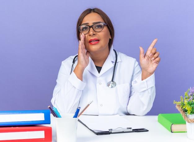 Ärztin mittleren alters im weißen kittel mit stethoskop mit brille, die ein geheimnis erzählt, wobei die hand in der nähe des mundes mit dem finger zur seite zeigt, die am tisch über der blauen wand sitzt?