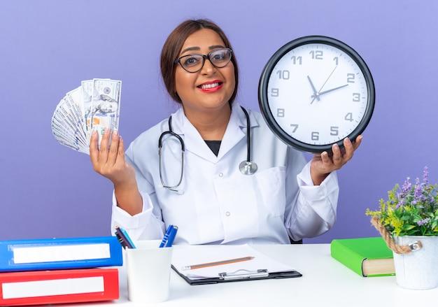 Ärztin mittleren alters im weißen kittel mit stethoskop mit brille, die eine wanduhr und bargeld hält und nach vorne lächelt, fröhlich am tisch über blauer wand sitzend