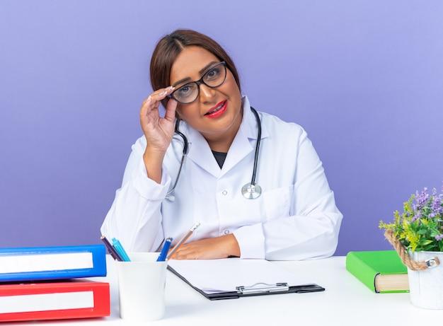Ärztin mittleren alters im weißen kittel mit stethoskop mit brille, die nach vorne schaut, glücklich und positiv lächelnd, selbstbewusst am tisch über blauer wand sitzend