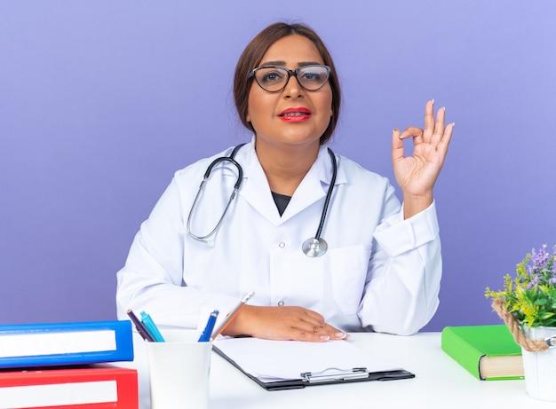 Ärztin mittleren alters im weißen kittel mit stethoskop mit brille, die nach vorne schaut und selbstbewusst lächelt, wenn sie am tisch über der blauen wand sitzt?