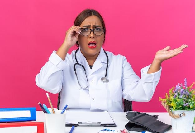 Ärztin mittleren alters im weißen kittel mit stethoskop mit brille, die verwirrt und unzufrieden aussieht, wenn sie mit ausgestrecktem arm am tisch mit büroordnern auf rosafarbenem hintergrund sitzt