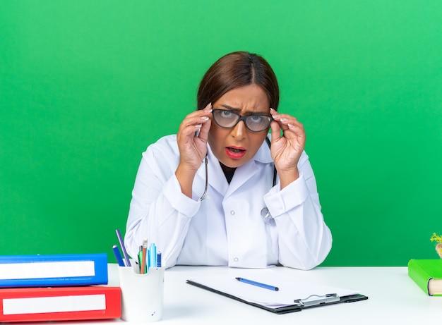 Ärztin mittleren alters im weißen kittel mit stethoskop mit brille verwirrt und sehr ängstlich am tisch über grüner wand sitzend