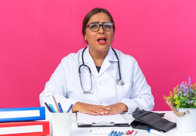 Ärztin mittleren alters im weißen kittel mit stethoskop mit brille verwirrt und sehr ängstlich am tisch über rosa wand sitzend