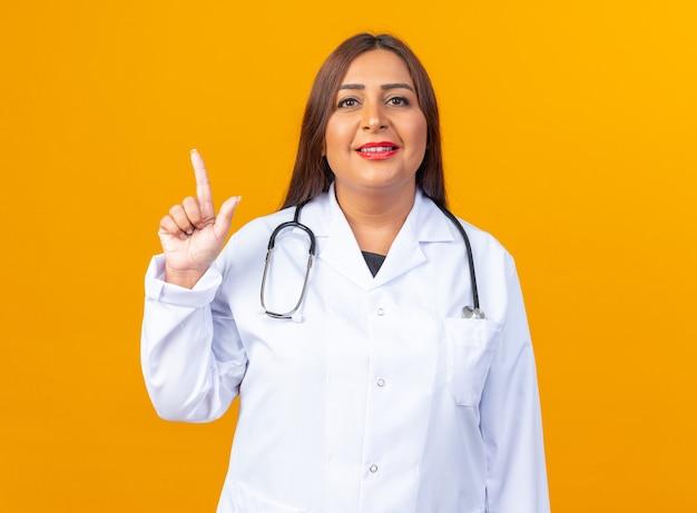 Ärztin mittleren alters im weißen kittel mit stethoskop mit einem lächeln auf dem intelligenten gesicht, das den zeigefinger über der orangefarbenen wand zeigt