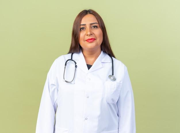 Ärztin mittleren alters im weißen kittel mit stethoskop mit selbstbewusstem gesichtsausdruck lächelnd stehend auf grün