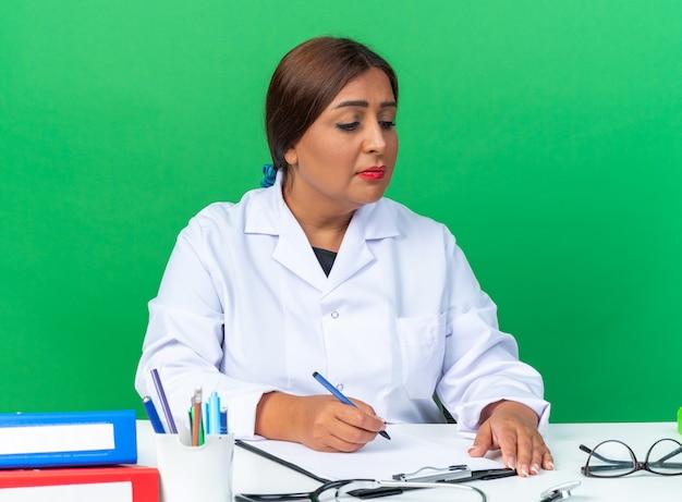 Ärztin mittleren alters im weißen kittel sitzt am tisch mit zwischenablage und dokumenten, die etwas über grünem hintergrund schreiben