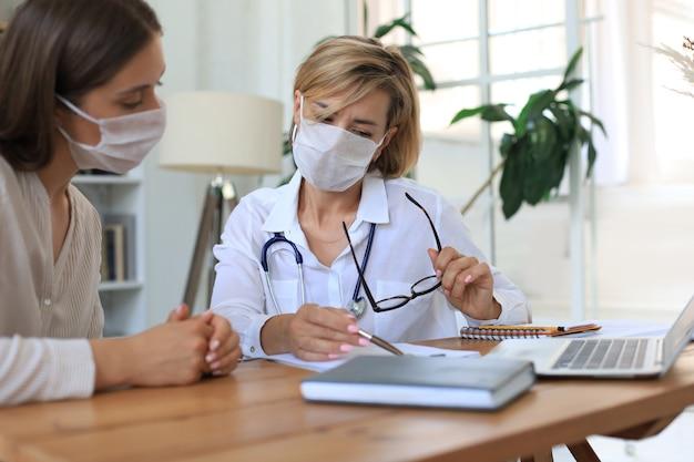 Ärztin mittleren alters in medizinischer maske in absprache mit dem patienten im büro.