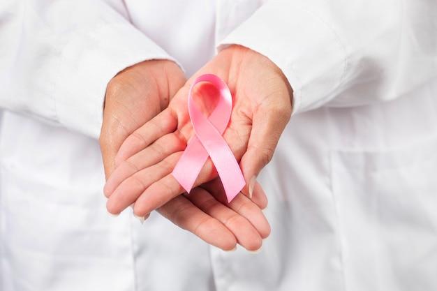Ärztin nahaufnahme auf händen halten brustkrebs-bewusstseinsband.