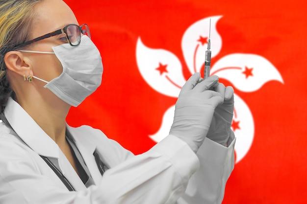 Ärztin oder krankenschwester in handschuhen, die spritze für impfung gegen die hongkong-flagge halten