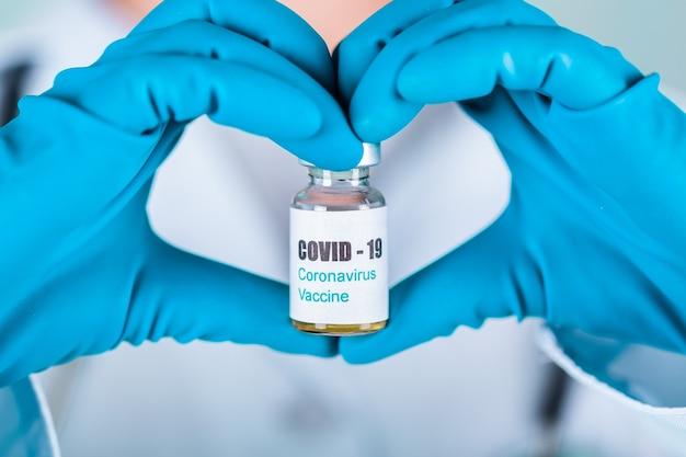 Ärztin oder krankenschwester in uniform und handschuhen mit gesichtsmaske, die im labor schutz in einer form der herzmedikamentenflasche mit covid-19 coronovirus-impfstoffetikett schützt