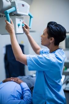 Ärztin richtet das gerät so ein, dass es über dem patienten röntgt