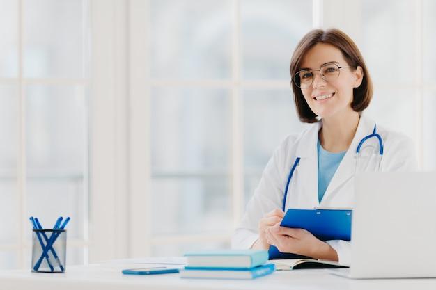 Ärztin schreibt rezept auf sonderform, arbeitet in einer privatklinik, trägt ein weißes medizinisches kleid