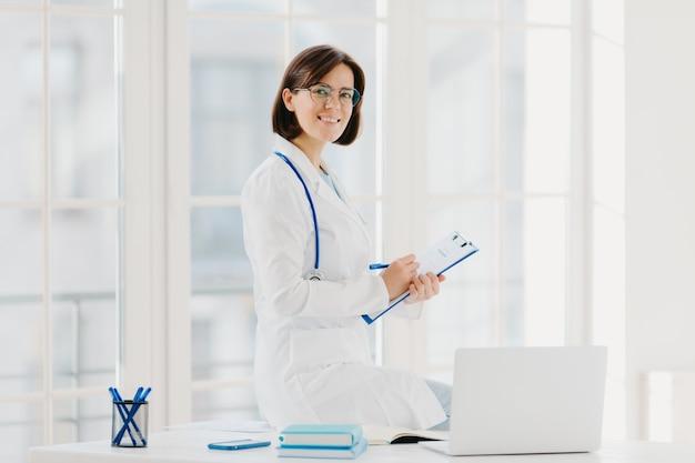 Ärztin sitzt auf dem tisch und schreibt informationen in die zwischenablage