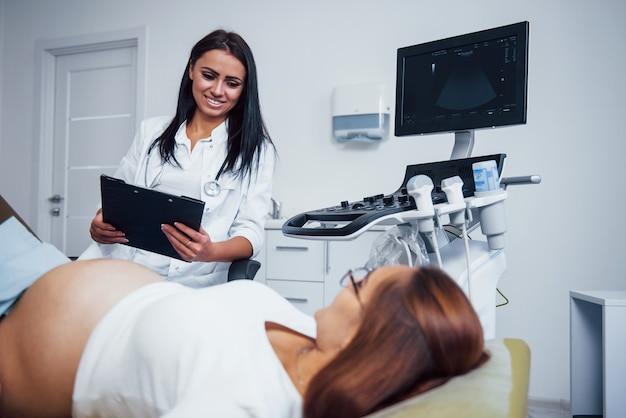 Ärztin spricht über ultraschallergebnisse für eine schwangere frau im krankenhaus.