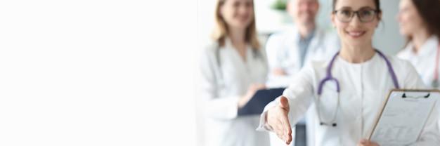 Ärztin streckt ihre hand für die zusammenarbeit vor dem hintergrund der medizinischen kollegen aus