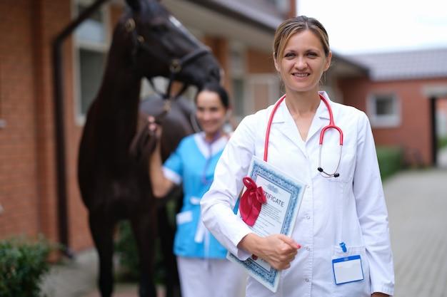 Ärztin tierarzt mit ärztlichem attest auf dem hintergrund des pferdes