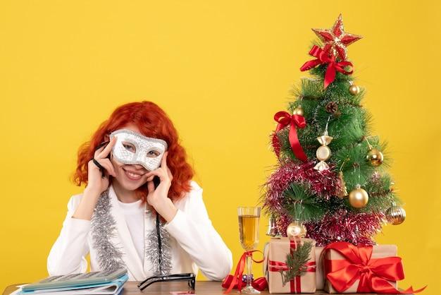 Ärztin trägt maske um weihnachtsbaum und präsentiert auf gelb