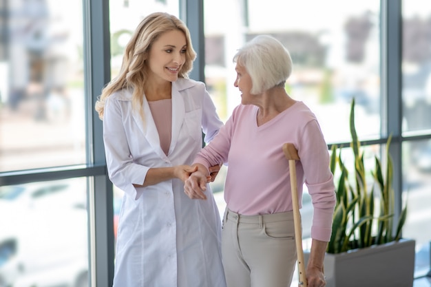 Ärztin und eine ältere frau mit einer krücke, die in einem korridor geht und spricht