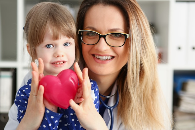 Ärztin und kleines kind halten in den armen