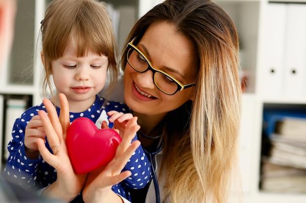 Ärztin und kleines kind halten spielzeugherz
