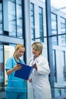 Ärztin und krankenschwester, die einen medizinischen bericht betrachten