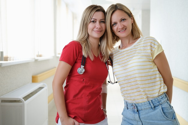 Ärztin und patientin, die im krankenhausflurporträt stehen