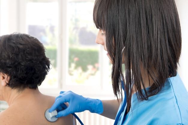 Ärztin untersucht eine patientin mit einem stethoskop