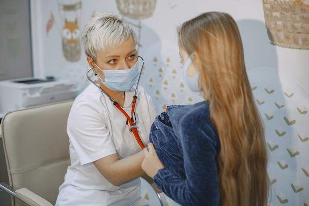 Ärztin untersucht kind. mädchen im büro eines kinderarztes.