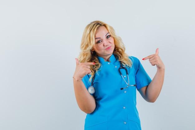 Ärztin zeigt auf sich selbst in blauer uniform und sieht selbstbewusst aus.