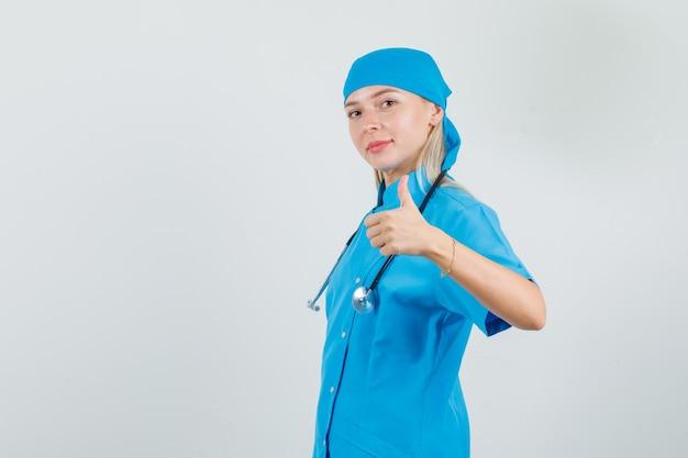 Ärztin zeigt daumen hoch in blauer uniform und sieht fröhlich aus.