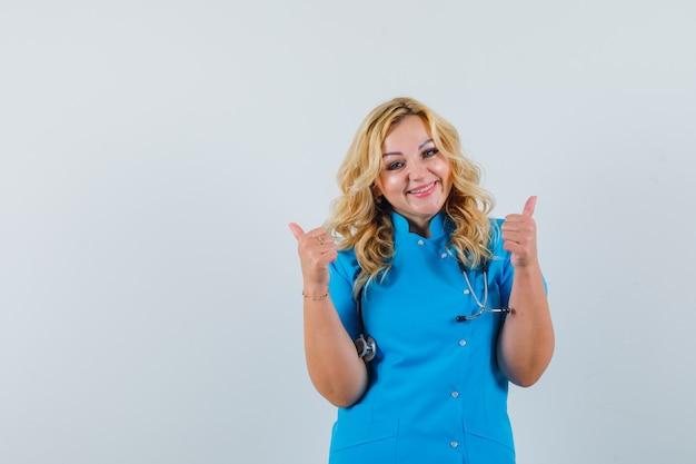 Ärztin zeigt daumen hoch in blauer uniform und sieht froh aus. platz für text