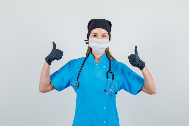 Ärztin zeigt daumen hoch in uniform, handschuhen, maske und sieht zufrieden aus. vorderansicht.