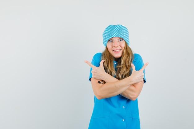Ärztin zeigt finger weg in blauer uniform und sieht fröhlich aus