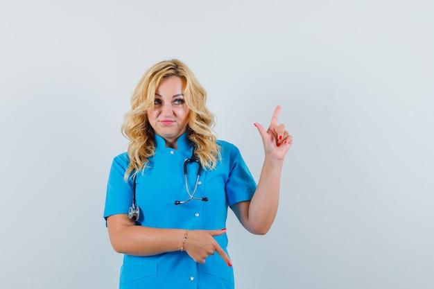 Ärztin zeigt in blauer uniform auf und ab und sieht zögernd aus