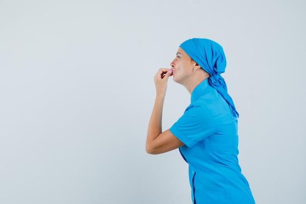 Ärztin zeigt köstliche geste in blauer uniform und sieht entzückt aus.