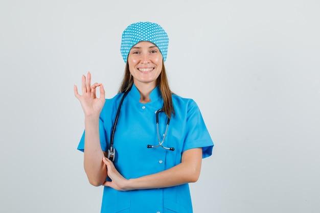 Ärztin zeigt ok geste in blauer uniform und sieht fröhlich aus. vorderansicht.