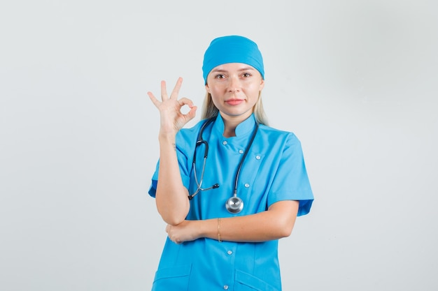 Ärztin zeigt ok geste in blauer uniform und sieht zufrieden aus